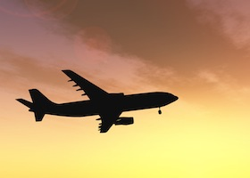 Concept or conceptual black plane, airplane or aircraft silhouette flying over sky at sunset or sunr