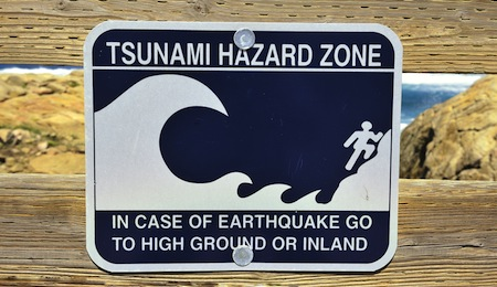 Tsunami Hazard Zone sign in case of earthquake go to high ground or inland Pebble Beach California