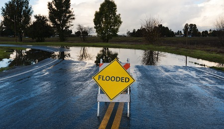 Flooded warning sign on an impassable road San Martin California