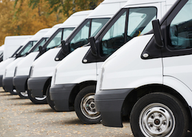 commercial delivery vans in row at parking place of transporting carrier shipping service company