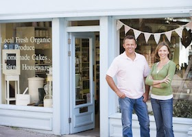Two business owner's standing in front of their store