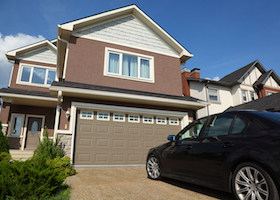 Car near the garage of new two-storied brown cottage with white roof