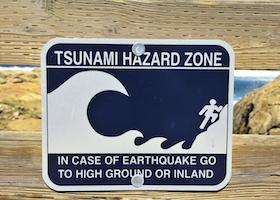 Tsunami Hazard Zone sign in case of earthquake go to high ground or inland Pebble Beach California
