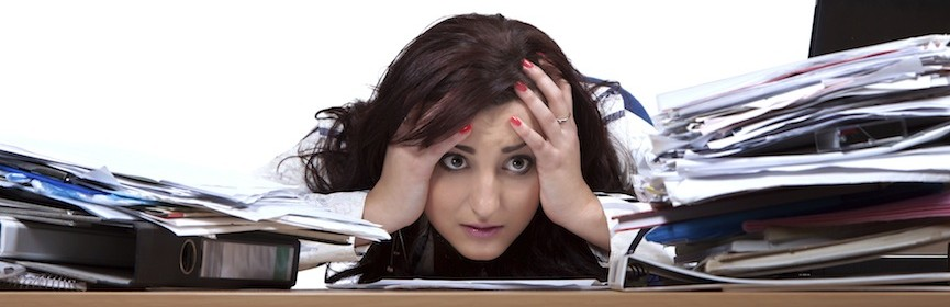 Young female office worker helplessly looking at the pile of papers with place for text