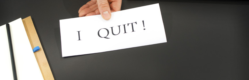 man holding an IO quit sign